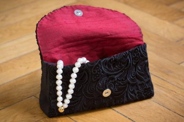 Clutch aus schwarzer Spitze mit rotem Seidenfutter und Perlenkette