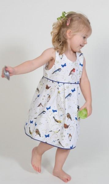 ärmelloses Kinderkleid, weiß mit bunten Vögeln, blaue Paspel an Oberteilnaht, in Bewegung