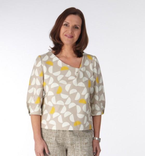 Bluse mit Falte aus beigem Stoff mit weißen und gelben Halbkreisen am Modell