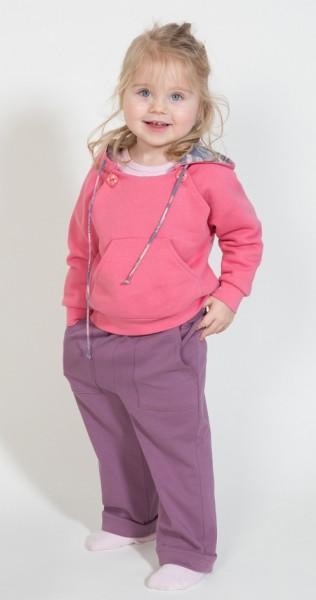 Mädchen mit fliederbeerfarbener Schlupfhose in Kombination mit einem rosa Kapuzensweatshirt.
